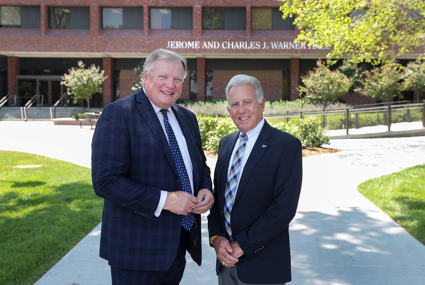 Doug Kristensen and Pete Kotsiopulos are pictured in front of Warner Hall on the UNK campus. The building is named after Charles J. Warner and his son Jerome Warner, two prominent former state senators who played a significant role in UNK's history.