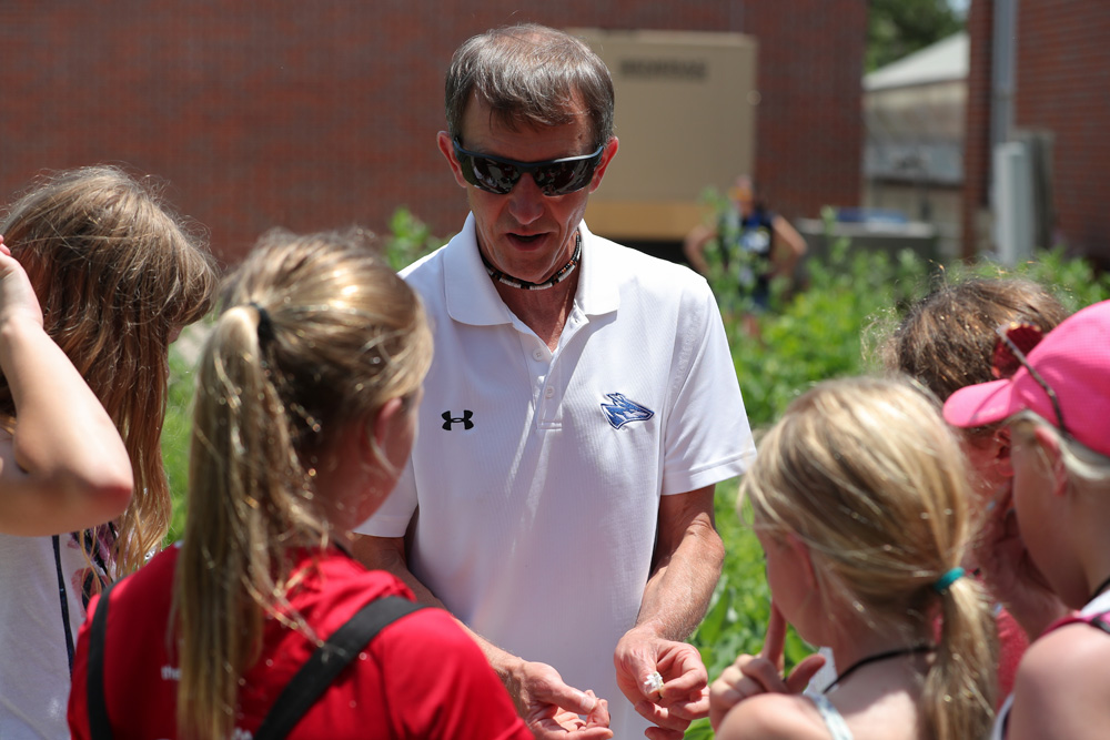 UNK biology professor Paul Twigg discusses plant life with PAWS University campers during their field trip to the campus greenhouse earlier this month. PAWS University participants visit different campus locations to learn about UNK and career options.