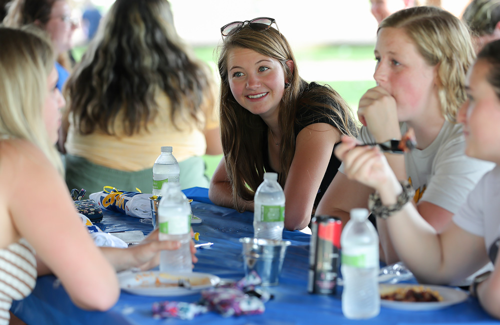 UNK incoming freshman Meg Schluns, center, chats with her new roommates and a Fraternity and Sorority Life member at a UNK Hangout Thursday at Harmon Park.