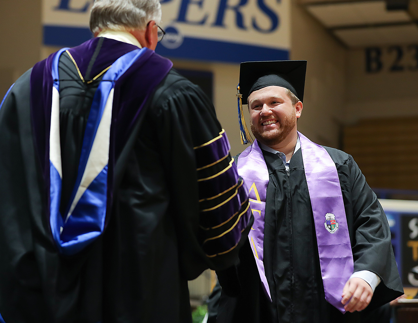 Brady Deprez, right, receives his degree from UNK Chancellor Doug Kristensen during Friday's summer commencement ceremony at the Health and Sports Center on campus.