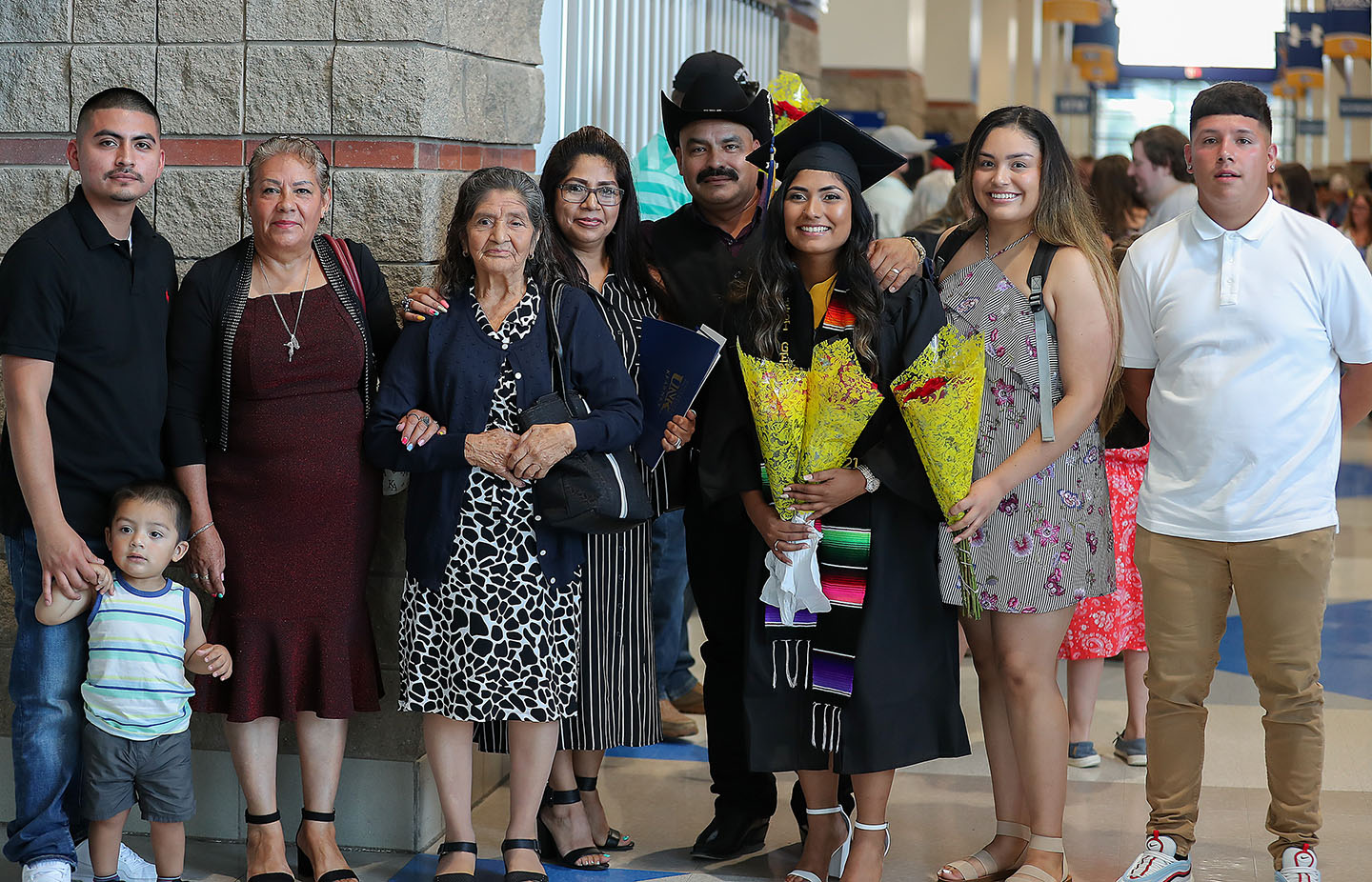 Edna Medina, third from right, poses for a photo with her family following Friday's summer commencement ceremony at UNK's Health and Sports Center.
