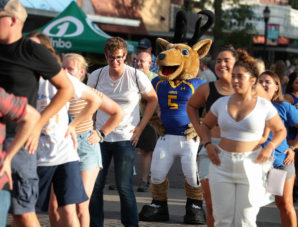 """Louie the Loper joins a group of UNK students dancing to """"Macarena"""" on Thursday evening during Destination Downtown. (Photos by Erika Pritchard, UNK Communications)"""