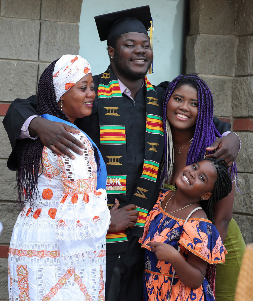 Hinwa Allieu poses for a photo with his mother and younger sisters following Friday's summer commencement ceremony at UNK.