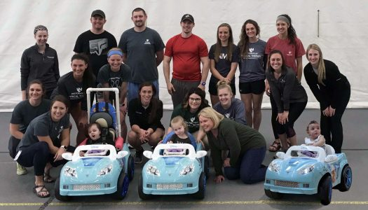 Students in the University of Nebraska Medical Center's Physical Therapy Education program in Kearney, along with engineering students at the University of Nebraska at Kearney, meet with the children and three cars the students modified.