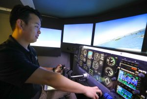 Jaehyun Kim, who graduated last week with a bachelor's degree in aviation systems management, demonstrates the Redbird flight simulator inside UNK's Otto C. Olsen building. The simulator allows aviation students to practice flying in different environments and it's an important tool when they're learning how to handle emergency situations. (Photo by Corbey R. Dorsey, UNK Communications)