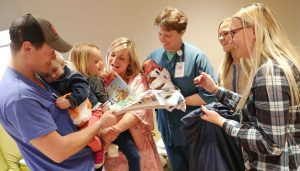 Jamie Cummings, a registered nurse at Kearney Regional Medical Center, holds newborn Titus Vest as members of the Vest family, from left, Talus, 2-year-old Haven, 5-year-old Estelle and Caitlin, receive gifts from UNK students Shyenne Cooper of North Platte, front right, and Gussie Rhoades of Giltner. Students in professor Jeanne Stolzer's child and adolescent development class delivered presents to hospital patients Wednesday as part of a service project. (Photo by Corbey R. Dorsey, UNK Communications)