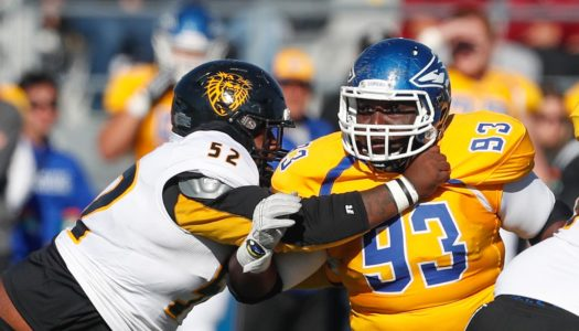 """UNK assistant football coach Levi Gallas calls Jordan Ingraham (93) the quarterback of the defensive line. """"When it comes to X's and O's and talking about scheme, he's asking about what the linebackers are doing, what the safeties are doing. He wants to know the whole picture,"""" Gallas said. (Photo by Corbey R. Dorsey, UNK Communications)"""