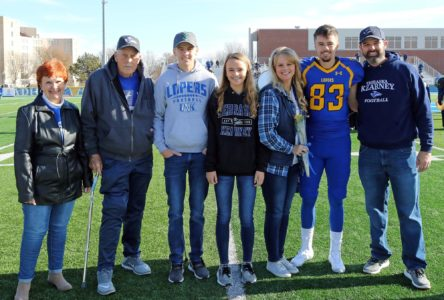UNK football player Mitch Carlson honors grandfather, a former Loper, on Senior Day