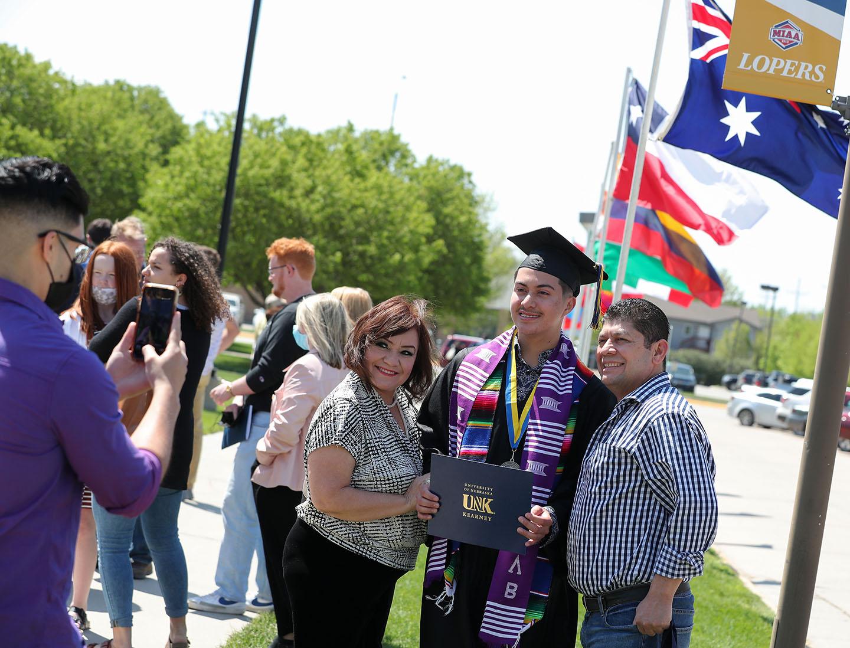 Mark Barrientos, en el centro, posa para una foto con su familia el viernes después de la ceremonia de graduación de primavera en el Centro Deportivo y de Salud UNK.  Barrientos se graduó en administración de empresas con énfasis en finanzas.
